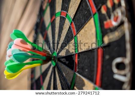 darts hitting bullseye on dartboard - stock photo
