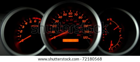 dashboard gauges lit at night - stock photo