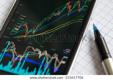 Data analyzing in stock exchange market: the charts and quotes on smartphone display.  - stock photo