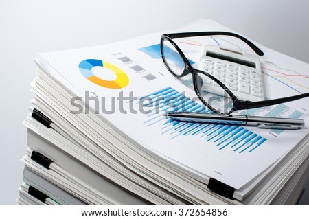 Data management. Document management. Business concept. Pile of documents on gray background. Graph, glasses, calculate and pen.  - stock photo