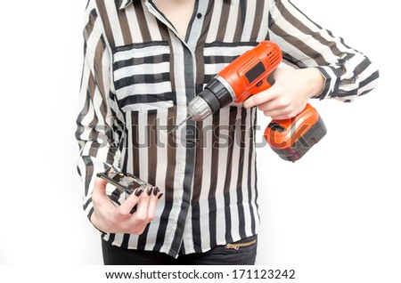 Data protection and loss suggested by a woman holding a hard drive and an electric screwdriver - stock photo