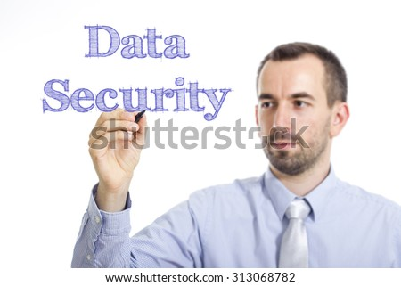 Data Security - Young businessman writing blue text on transparent surface - stock photo