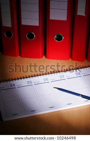 Date book on desck with red files on background - stock photo