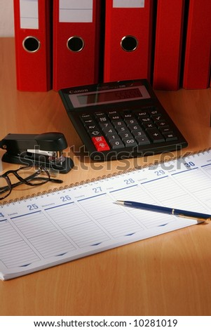 Date book on desk with red files on background - stock photo