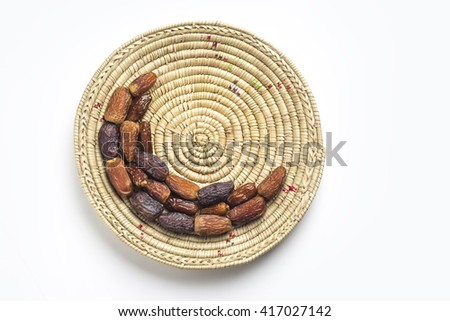 Date fruits arranged in moon shape on a straw plate. Islamic festive food and it's significance. - stock photo