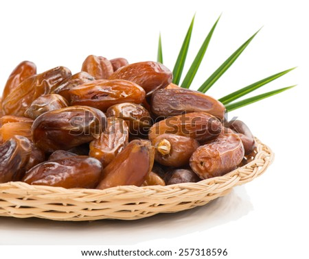 Date fruits in a wicker tray  isolated on white background, selective focus - stock photo