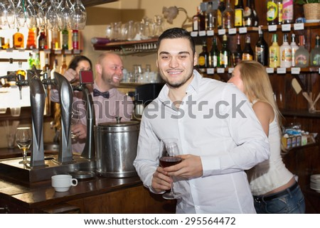 Date of young positive couple drinking wine at bar and smiling - stock photo