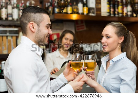 Date of young smiling couple drinking wine at counter in bar. Focus on girl