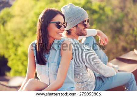 Date on the roof. Beautiful young smiling couple sitting back to back on the roof of the building