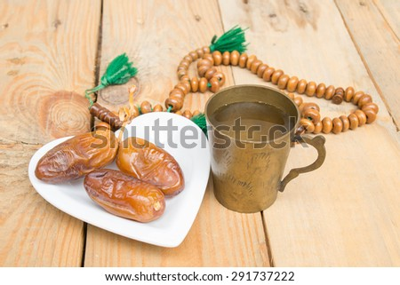date palm on the wood. Fasting is obligatory for adult Muslim in Ramadan. Muslim will breaking their fasting after sundown with a date palm or with water to  following the tradition. - stock photo