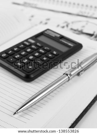 Datebook, metallic pen, calculator, glasses and calendar. Black and white picture. - stock photo