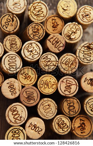 Dated wine bottle corks on the wooden background. Close up