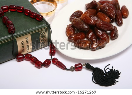 Dates, a coffee cup waiting to be filled, beads, and a copy of the Holy Qur'an, all are symbolic of the Muslim fasting month of Ramadan and of the breaking of the fast each evening at Iftar. - stock photo