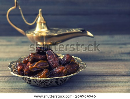 Dates and golden arabian lamp on wooden background. Oriental food. Retro style toned picture. Selective focus - stock photo