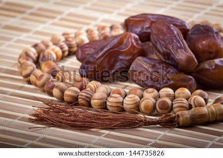 Dates and muslim prayer beads on matting - stock photo