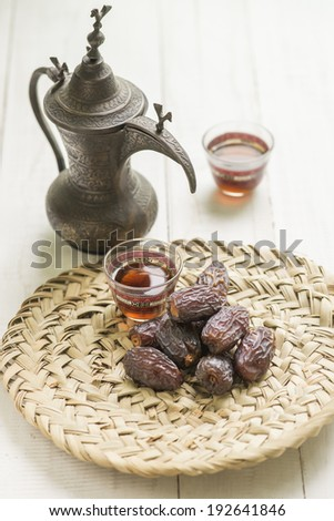 Dates displayed on palm - platter with traditional coffee set - stock photo