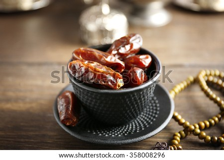 Dates fruit and rosary on served wooden background, close up - stock photo