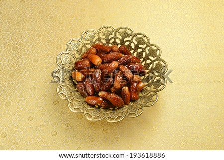 Dates in an ornamental bowl. - stock photo