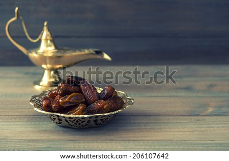 Dates in golden bowl and arabian lamp on wooden background. Retro style toned picture - stock photo