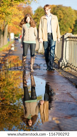 Dating couple and their reflection in a puddle - stock photo