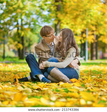 Dating couple in yellow leaves on a bright fall day - stock photo
