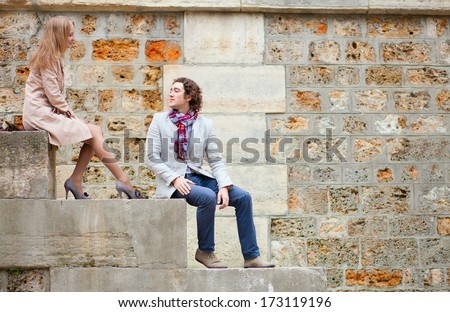 Dating couple sitting on the Seine embankment