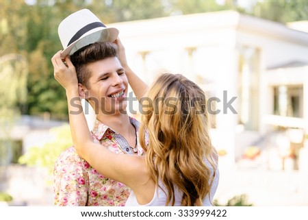Dating. Loving couple outdoors. Young woman taking off boyfriend's hat. - stock photo