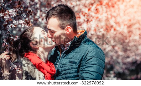 Dating. Young woman and man walking, couple in love relaxing in blossoming cherry trees park at sunny spring day