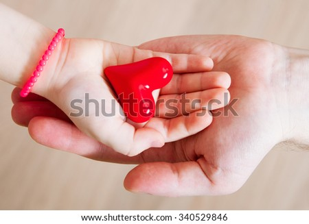 Daughter and her father holding a red heart in their hands, neutral background