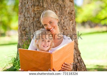 Daughter and her mother looking at their album photo - stock photo