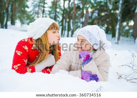 daughter and mother are happy together. Mom and daughter lying on the snow in winter. girls in winter forest. Two girls having fun in winter, winter fun outdoors - stock photo