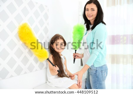 Daughter and mother cleaning dust in room - stock photo