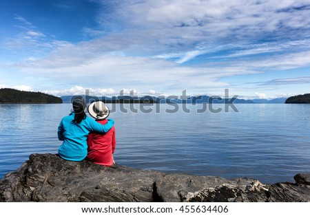Daughter and mother, facing away from camera, enjoying the outdoors on a beautiful day with lake and mountains in background.  Selective focus on backs of people.  - stock photo