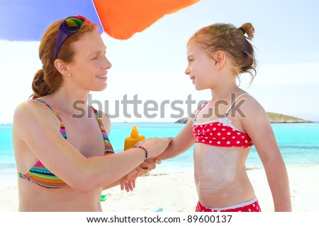 daughter and mother in beach with sunscreen in bikini - stock photo