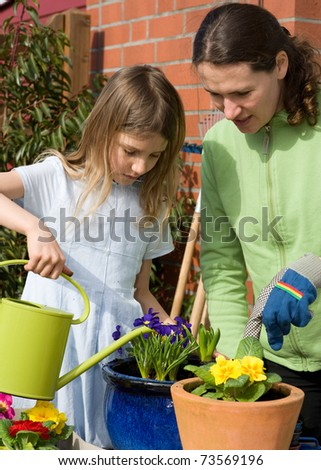 Daughter and mother planting flowers in garden
