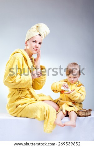 Daughter and mother putting makeup after bathroom - stock photo