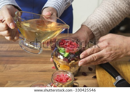 Daughter assisting her mother with preparing sweet preserves and pouring honey on dried fruit mix. In the jar there are walnuts, cranberries, figs, melon and papaya. - stock photo