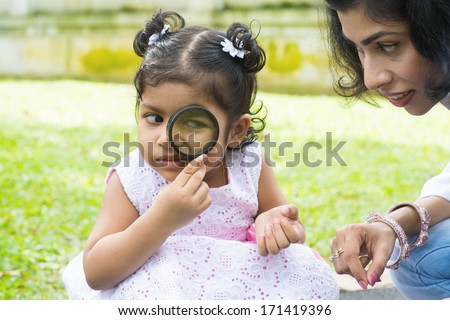 Daughter at outdoor green park with mother. Cute Indian girl peeking through magnifying glass with parent. - stock photo