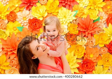 daughter at the hands of the mother against the backdrop of colorful flowers made of paper - stock photo
