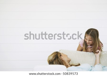 Daughter bending above mother lying on couch, half length - stock photo