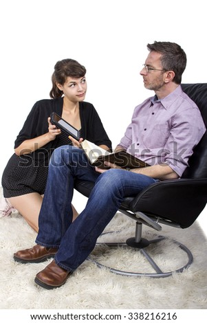 Daughter comparing tablet e-reader with fathers traditional book.  The girl is trying to convince her dad to switch to new technology. - stock photo
