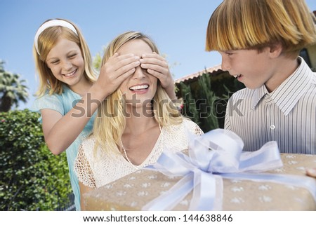 Daughter covering mother's eyes as son holds a gift in front of her - stock photo