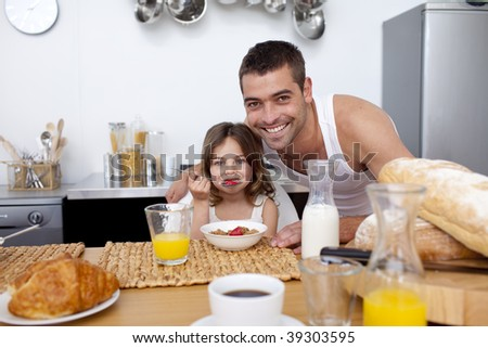 Daughter eating cereals and fruit in kitchen with her father