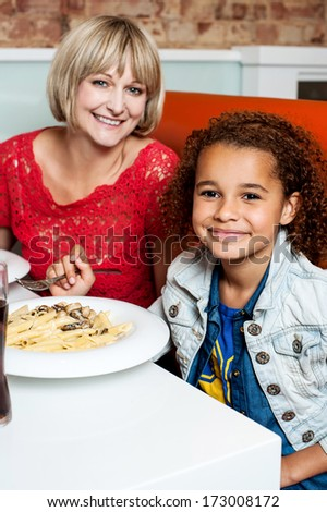 Daughter enjoying meal with her mother - stock photo