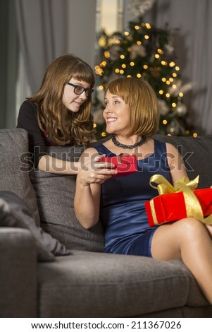 Daughter giving Christmas present to mother at home - stock photo