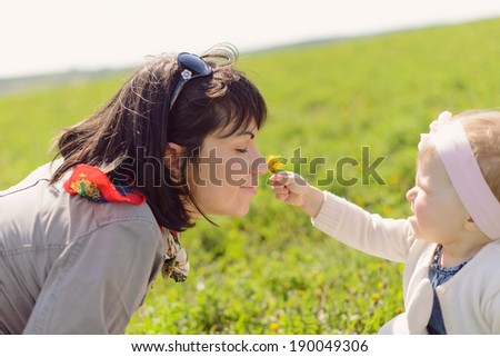 daughter giving dandelion to her mother to smell - stock photo