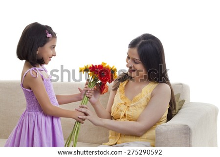 Daughter giving flowers to pregnant mother - stock photo