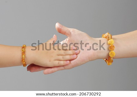 Daughter hand playing with mother hand - stock photo