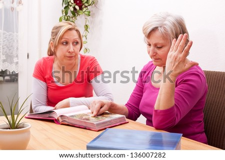 daughter help senior to remember - stock photo