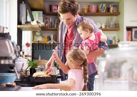 Daughter Helping Father To Cook Meal In Kitchen - stock photo
